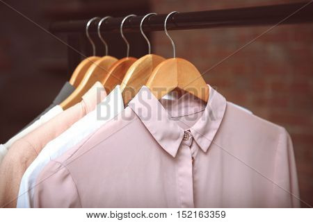 Hangers with female shirts on clothes rail, closeup