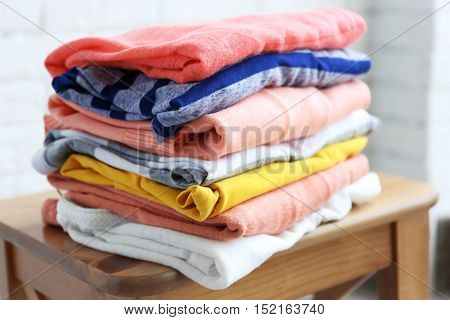 Pile of clothes on wooden stool, closeup