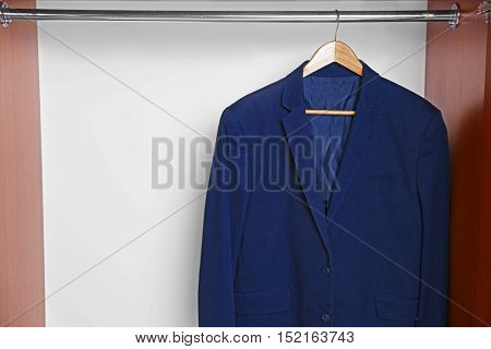 Hanger with male jacket on clothes rail in wardrobe