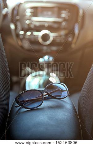 Sunglasses on car panel, closeup