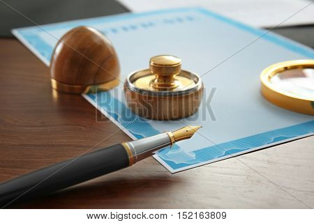 Stamp, magnifier, ink pad, pen  and document on notary public table