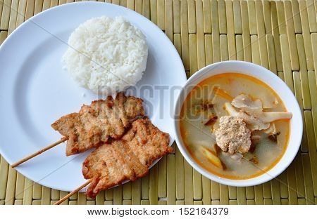 grilled pork on rice and fish egg with mushroom spicy soup