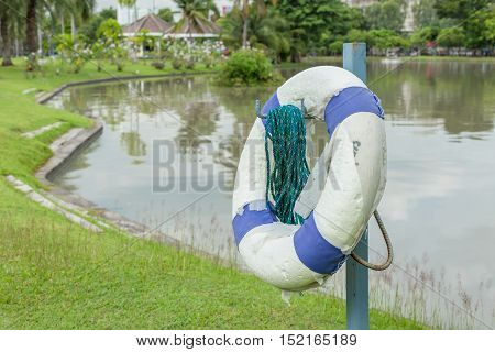 Life Preserver On Pole At Lake At Day Time.