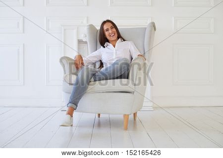 Close-up of Caucasian modern positive woman whose face shows kindness, she crossed one leg while sitting in the armchair