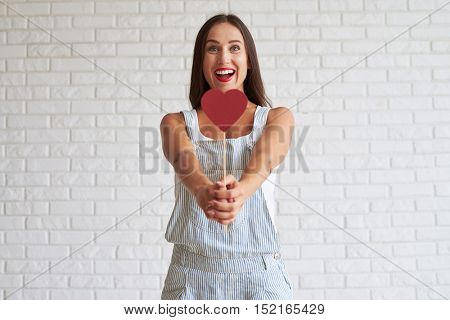 Happy beautiful brunette dressed in singlet with overalls and holding red paper heart in front of her, white brick wall on background