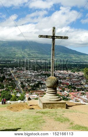 Antigua, Guatemala - June 16, 2011:Cerro de la Cruz is a religious stone cross monument placed where you can overlook the city of Antiqua in Guatemala with the Agua volcano in the background.
