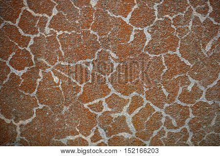 Old russet color on concrete and with fissures.