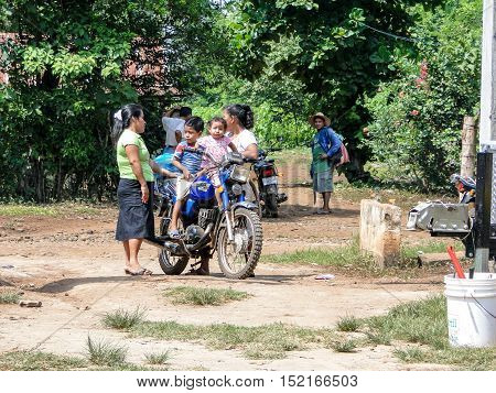La maquina, Guatemala - June 16, 2011: Family with young kids on a motor bike on a dirt road in La maquina, Guatemala. Editorial use only.