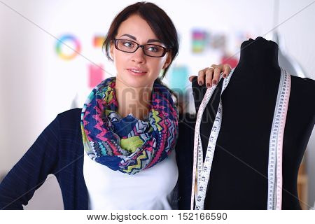 Smiling fashion designer standing near mannequin in office .