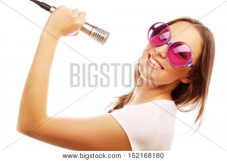 Happy singing girl. Beauty woman wearing white t-shirt and big sunglasses with microphone over white background. ipster styl