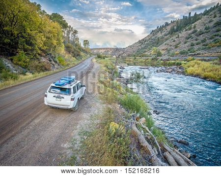 BURNS, CO, USA - SEPTEMBER 28, 2016: Toyota 4Runner SUV (2016 Trail edition) carrying  a paddleboard on a shore of the Colorado River in fall colors.