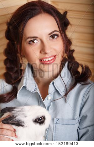 Lovely girl with a rabbit in his arms. Pets.