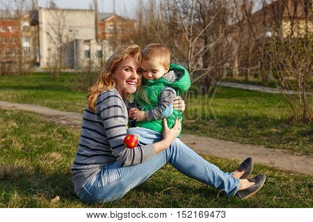 Mother and son sitting on the lawn and embracing in autumn park. Family time. Happiness of childhood and motherhood. Outdoor Activities.