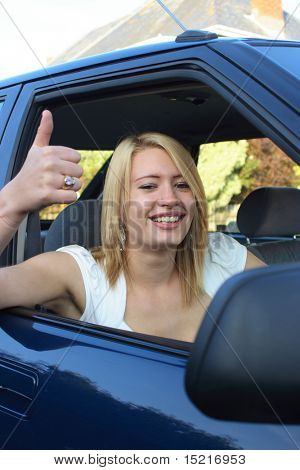 Happy teenager gives a smile and a big thumbs up seated in a car after passing her driving test.