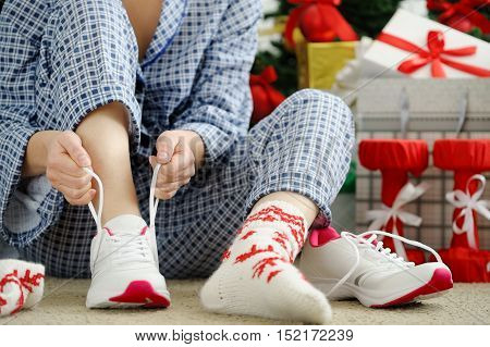 Woman In Pajamas Ties The Laces Of Athletic Shoes.