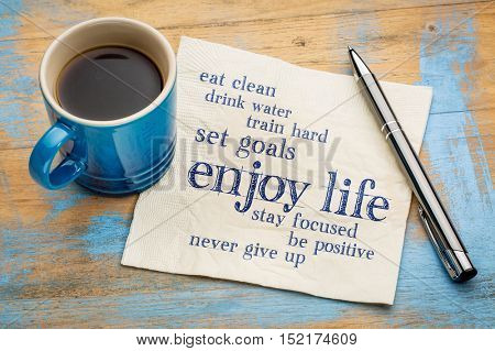enjoy life - healthy lifestyle word cloud on a napkin with a cup of coffee