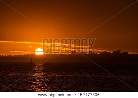 Orange Hues Of Tropical Sunset Over Water With Cityscape Silhouette