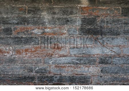 Antique brick wall with red bricks showing though layers of gray paint. Abstract background of building fragment in Toulouse, France.