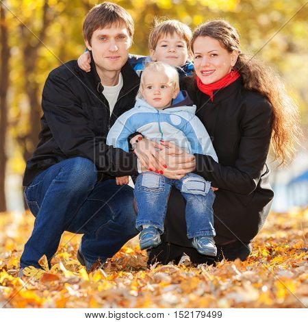 Happy family walking in the autumn park. Beauty nature scene with colorful foliage background, yellow trees and leaves at fall season. Autumn outdoor lifestyle. Happy family relax on fall leaves