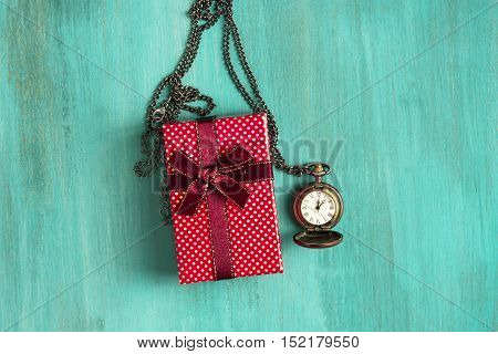 A photo of a present and a vintage chain clock showing the time a little past midnight. A New Year or Christmas greeting card on a teal background with copyspace