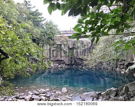 An all natural serenity pool with aqua clear blue water. Photo taken at Cheonjiyeon Falls in Jeju Island, Korea on October, 2016.