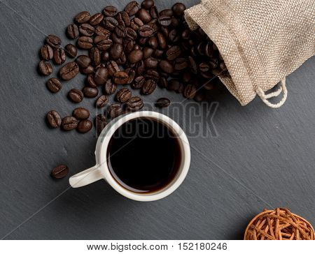 Heap coffe beans and cup of fresh coffee on dark stone background