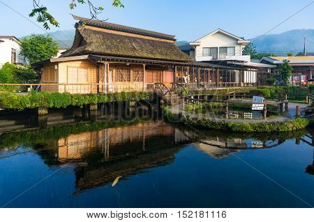 Oshino, Japan - September 2, 2016: Oshino Hakkai Fuji Five Lakes. Japan countryside landscape of traditional thatch roof farmhouses and pond with crystal clear blue water