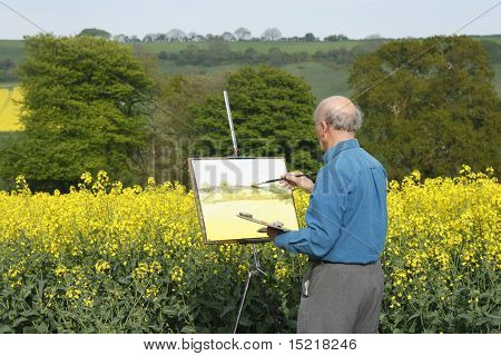 Senior male artist painting in a field full of bright yellow rapeseed or canola.