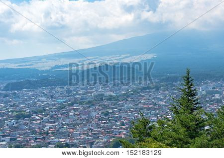 Fujiyoshida city with foot of Mount Fuji covered in clouds view from above Yamanashi prefecture Japan