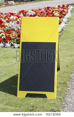 Blank yellow sandwich board in a park add your own text.