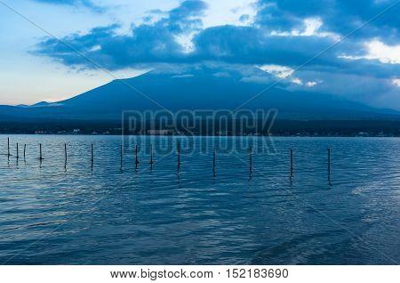 Mount Fuji on dusk with lake Yamanaka with fishing nets on the foreground. Lake Yamanaka popular tourist destination for Mount Fuji the highest mountain in Japan. Honshu Yamanashi prefecture Japan