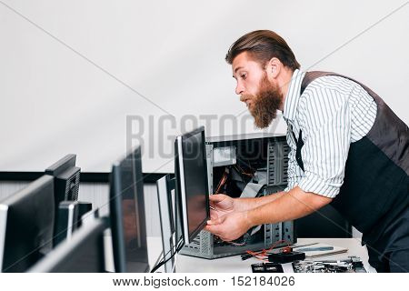 Programmer connecting monitor and CPU in office. System administrator fixing electronic equipment for company work