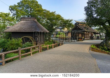 Oshino Hakkai historic village traditional thatch roof farmhouses and water wheel. Fuji Five Lakes Japan