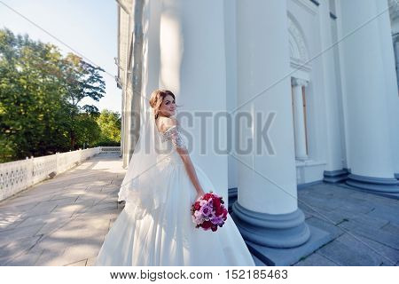 Beauty bride in bridal gown with bouquet and lace veil in the nature. Beautiful model girl in a white wedding dress.