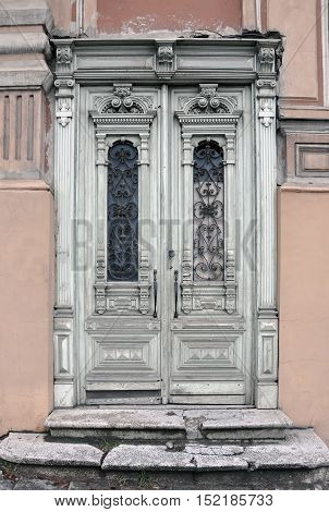 Old vintage door of an historic building with carved wooden decorations painted in white. Vilnius, Lithuania.