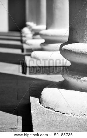 White classical column bases with contrasting shadows in perspective. Selective focus.