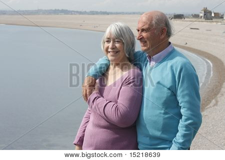 Senior couple embrace by the sea.