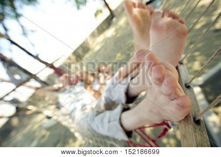 Feet of woman and man relaxing in hammock