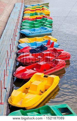 Row of multicolored catamarans at the pier
