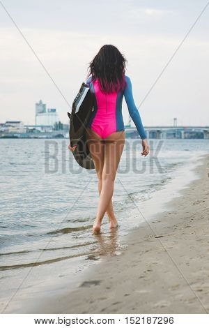 Beautiful sexy surfer girl with pink hair on the beach at sunset