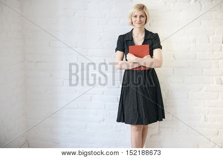 Smiling young woman standing against white wall, holding folder.