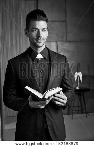 Portrait of good-looking young catholic priest holding book smiling.