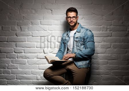 Young goodlooking caucasian man in glasses sitting at white brick wall, reading book, plenty of copyspace.