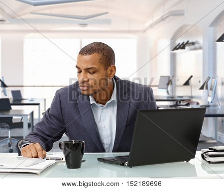 Focused, serious black businessman working at business office desk. Sitting, looking at paperwork. Laptop, mug on table. Suit no tie, copyspace.