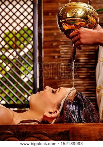 Young woman having pouring oil massage in India spa treatment. Shirodhara Pouring oil on head. Green plants outside.