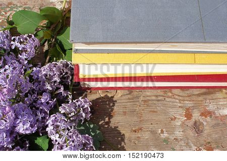 A stack of books and flowers of a lilac in the garden on wooden background.