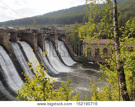 Old dam on the river on a background of mountains and woods on a sunny day