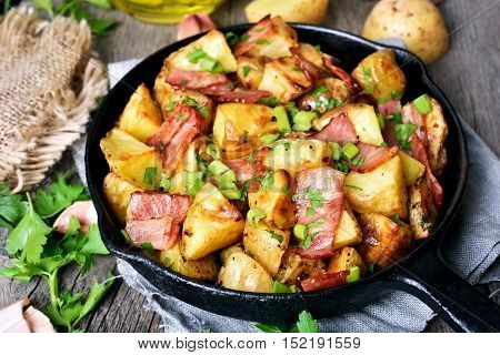Fried roasted potatoes with bacon onions in frying pan close up view