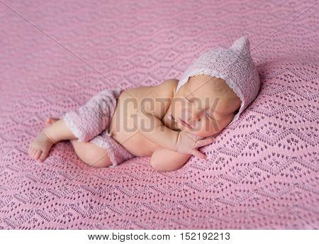 lovely sleeping newborn baby in pink hat and panties on pink blanket