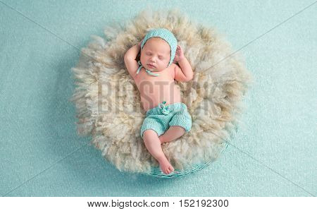 funny newborn boy sleeping with hands behind his head on round fluffy bed